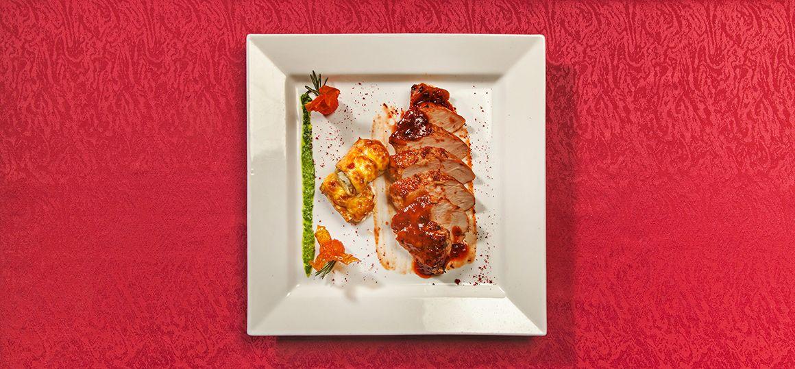 Свиная вырезка жареная под соусом с рулетиками из баклажан и жареными томатами