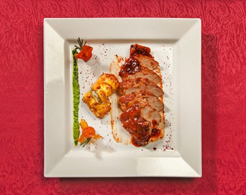 Fried pork fillet under sauce with aubergine rolls and fried tomatoes